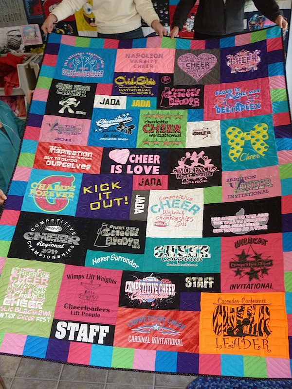 A cheerleading T-shirt quilt with a colorful border by Too Cool T-shirt quilts