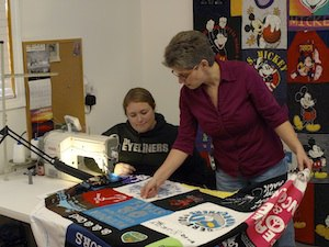 Two quilt makers looking at a T-shirt quilt while it is being sewed.