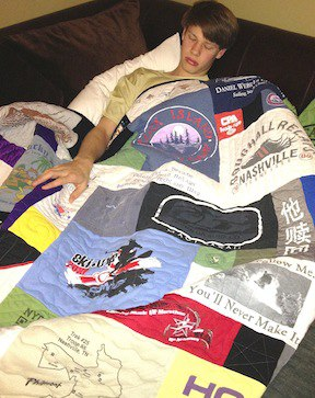 A young man sleeping under a T-shirt quilt on a couch.