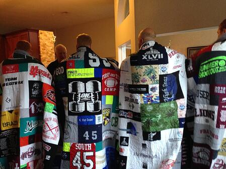 A group of 4 adult brothers wrapped in their T-shirt quilts as seen from the back.