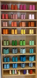 Thread colors arranged for T-shirt quilts on a shelf