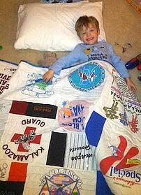 cute little boy with a Too Cool T-shirt Quilt.