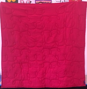 Crimson fabric that looks fuchsia on the back of a campus quilt