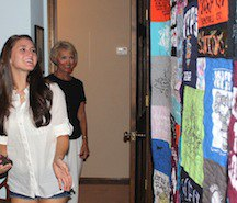 A young woman surprised with a T-shirt quilt as a gift.