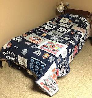 This is a firefighter's T-shirt quilt on the bed at the firehouse.