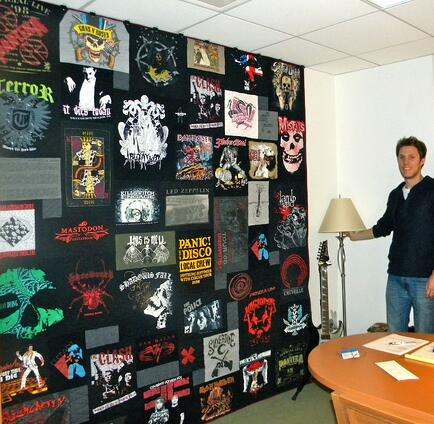 This concert T-shirt quilt hangs on the wall of a professional concert organizer.