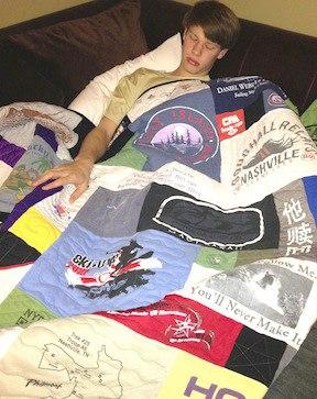 boy sleeping under a T-shirt quilt.