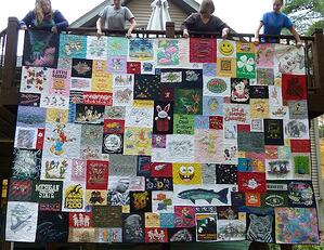 This is one of the worlds's largest T-shirt quilt photographed hanging over a deck railing.