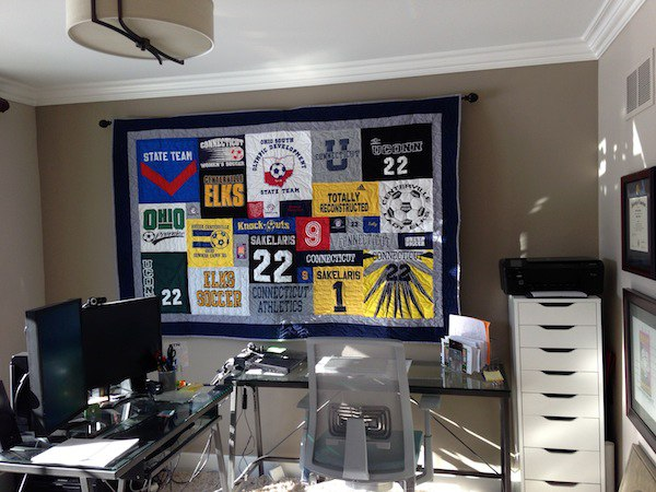 t-shirt quilt hanging in office