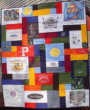 An example of a T-shirt quilt with blank block fillers to increase the size of the quilt.