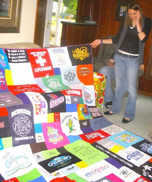 A young woman sees her T-shirt quilt for the first time. Hint - she loves it!