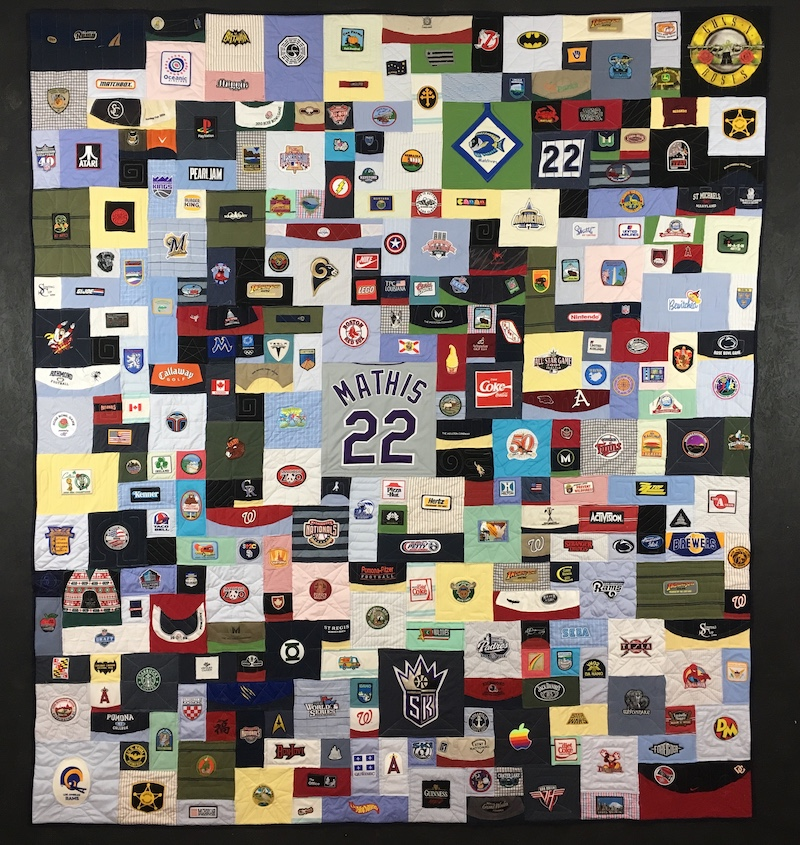 Baseball hats and patches made into a quilt.