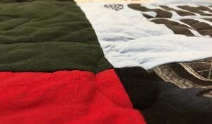 A T-shirt quilt made with high loft batting. The low areas are where the stitching is and the high areas are where there is no stitching.