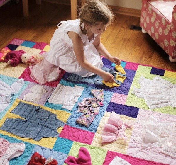 Girl playing with items on a T-shirt quilt