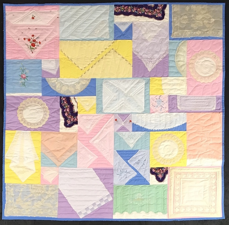 Hankies made into a quilt on a pastel background
