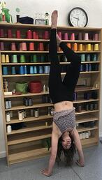 Long-arm T-shirt quilter doing a hand stand in front of thread