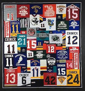 A quilt made from hockey jerseys with a lot of the player's numbers represented.