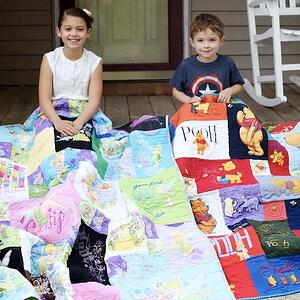 Two young kids hanging out with their T-shirt quilts on their front porch.