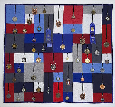 Medals hanging on a quilt.