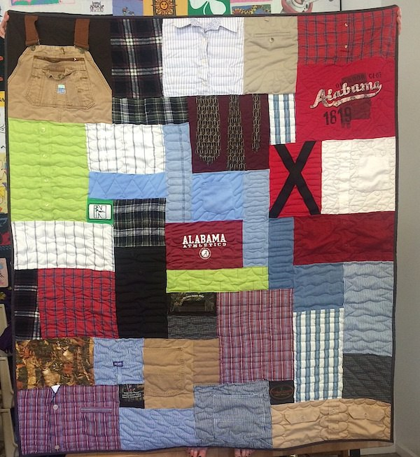 A clothing memorial quilt that includes dress shirts, overalls, suspenders and jeans.