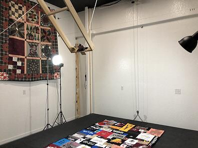A shot of the photo studio at Too Cool T-shirt quilts in operation. This shows the black stage and the camera in mid-lift to the ceiling.