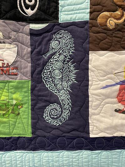 The front of a T-shirt quilt with a sea horse that has been traced.