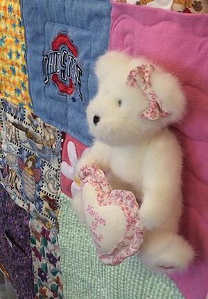 Stuffed bear on a memory T-shit quilt