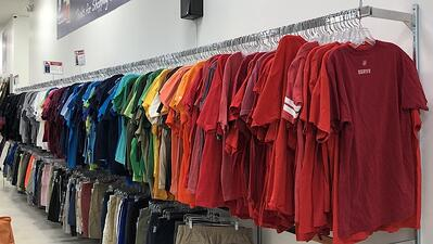A huge rack of T-shirts color coordinated at a resale shop