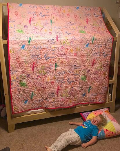 back of triangle quilt with girl and pillow