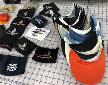 getting baseball caps ready to put into a T-shirt quilt. First, remove the bills.