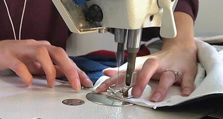 close up of a person sewing a T-shirt quilt