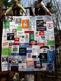 2 women holding a T-shirt quilt over the railing of a deck.