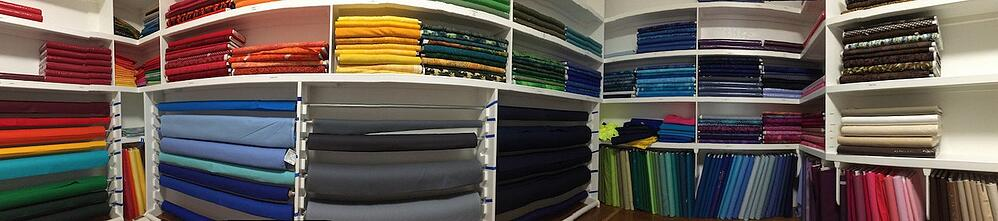 This is a panoramic photo of the fabric room at Too Cool T-shirt Quilts. It shows some of the backing color choices available.
