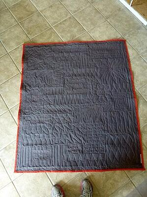 This is the back of a T-shirt quilt photographed on the tile floor.