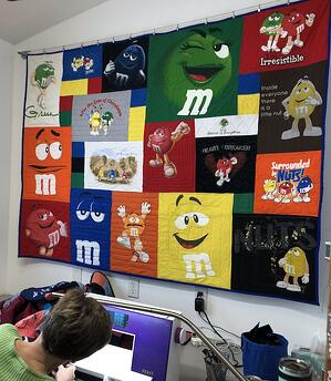 m&m T-shirt quilt hanging in binding room