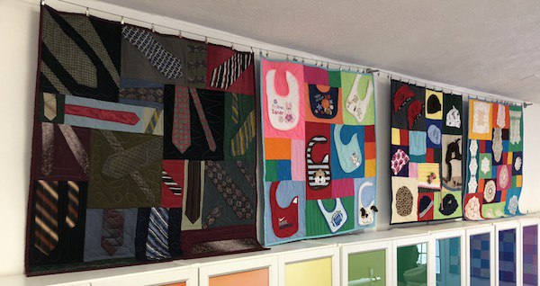row of mini quilts hanging here at too cool