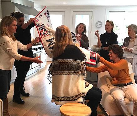 women opening a T-shirt quilt at a party